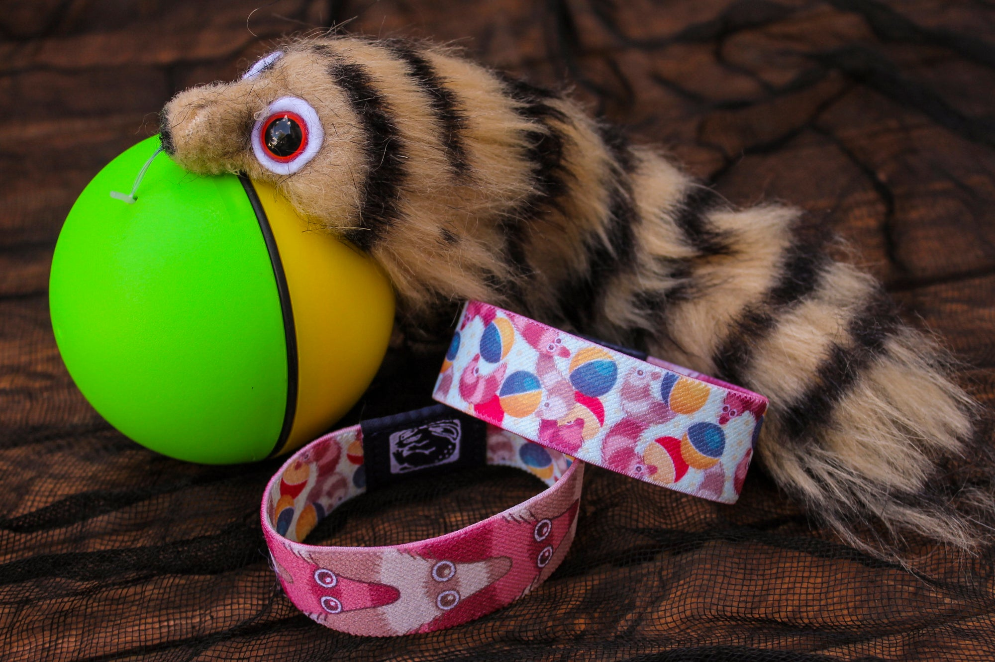 Two identical, reversible thin fabric bracelets flipped in opposite directions to show the complementing pattern set. The one on the left's outward facing pattern is of overlapping brown and blush striped weasel ball critters with big shiny eyes. The one on the right has an outward facing design of a whole mess of weasel-balls twirling and tumbling on a light-colored background. They are in front of a real-life weasel ball.