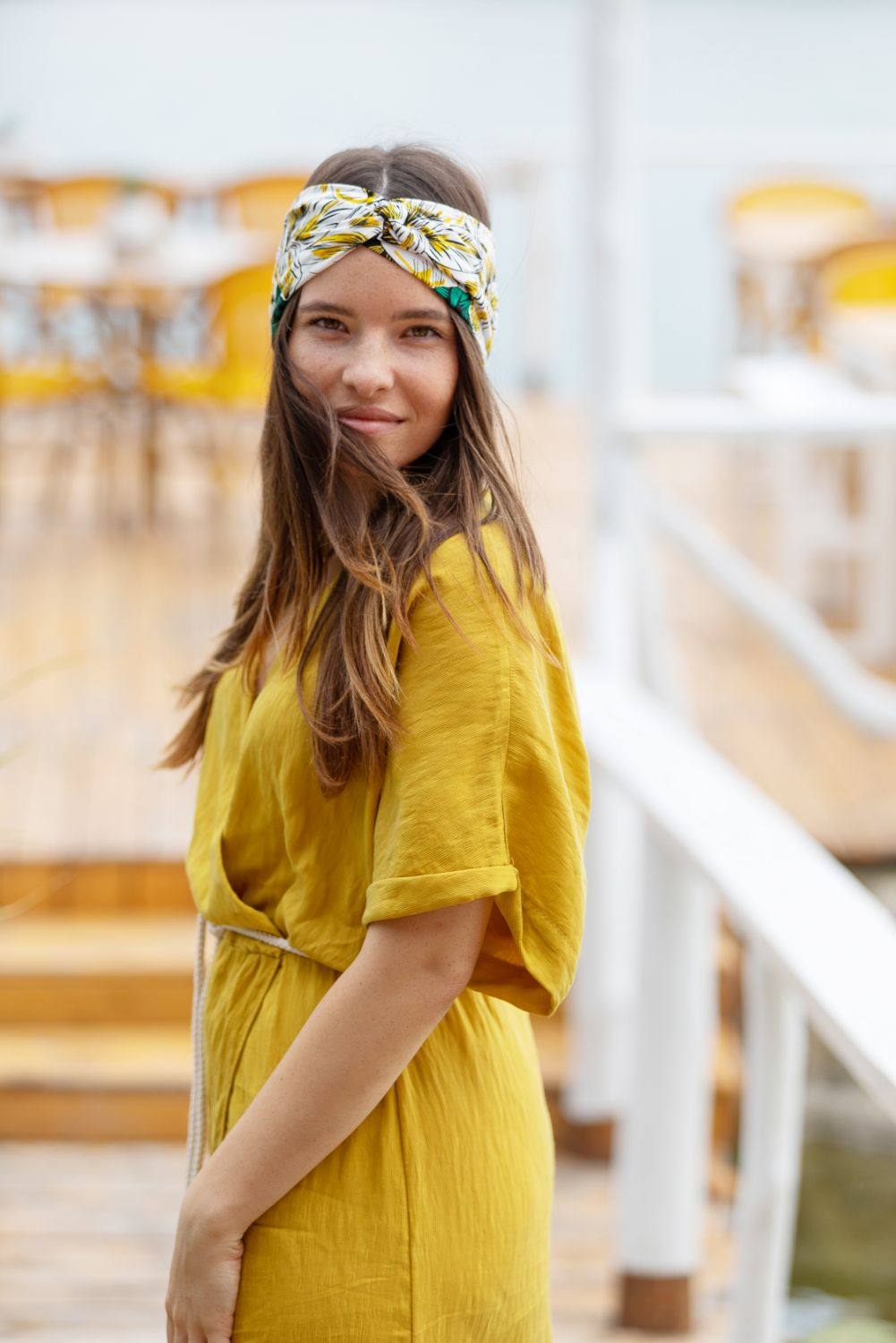 a female model is wearing a black and yellow flower headband