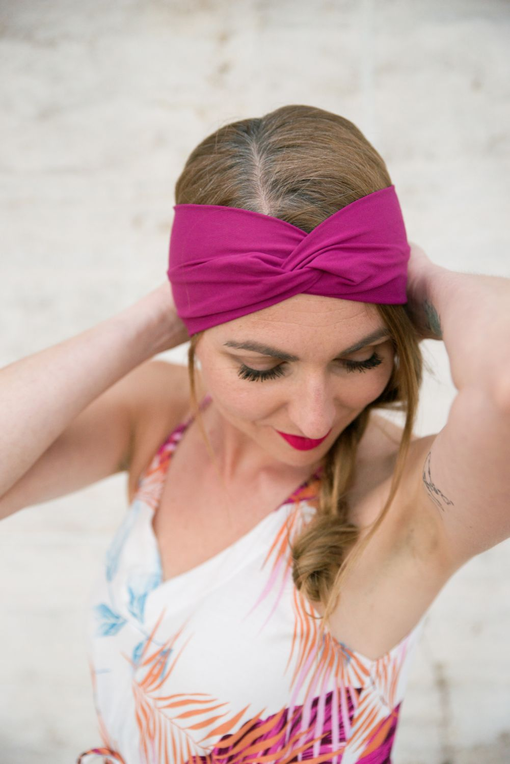 a female model is wearing a magenta pink headband