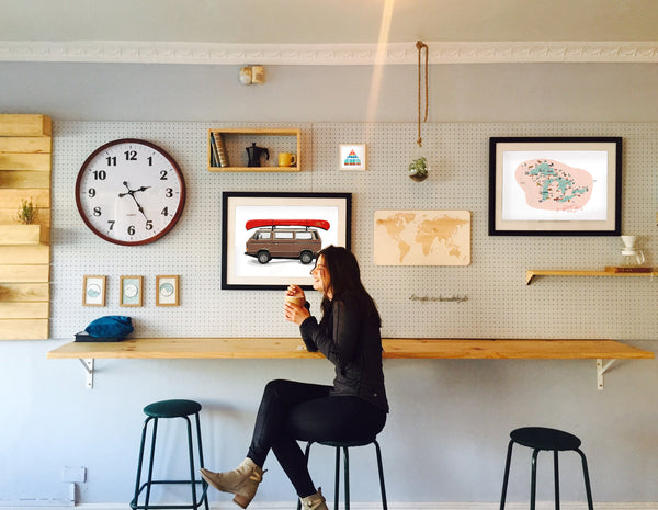 Girl sitting in cafe with Great Life prints on wall