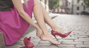 Woman in pink skirt sitting down outside with high heel pain