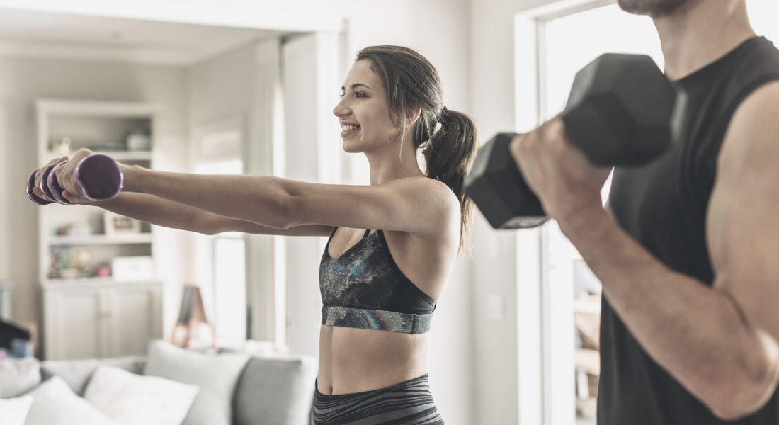 Couple working out in living room with arm weights