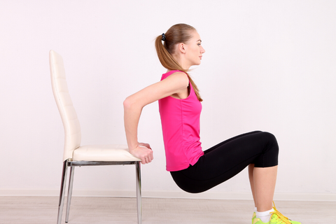 Woman doing chair dips inside