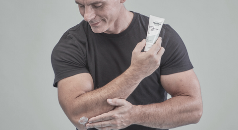 Athletic man using Maddyn topical CBD cream on elbow