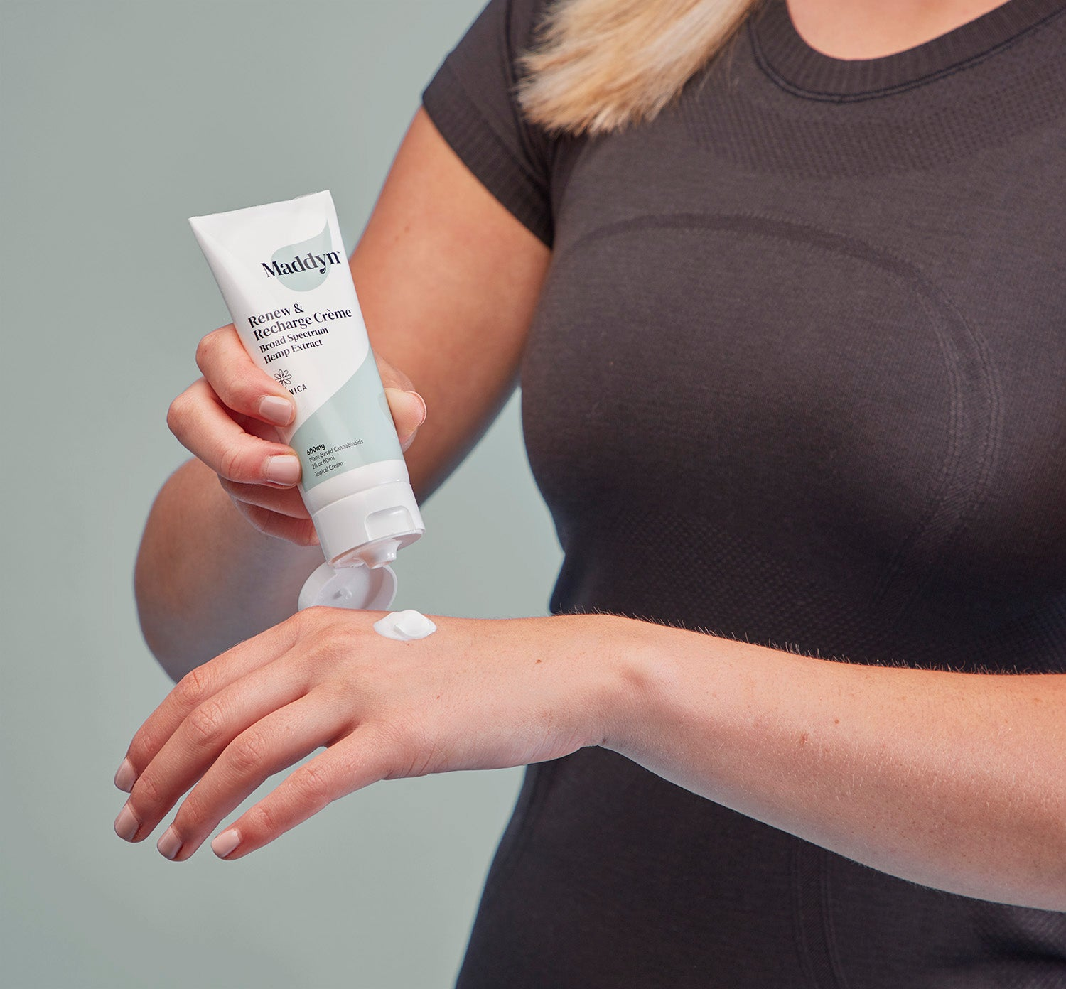 Woman using Maddyn topical CBD cream on hand