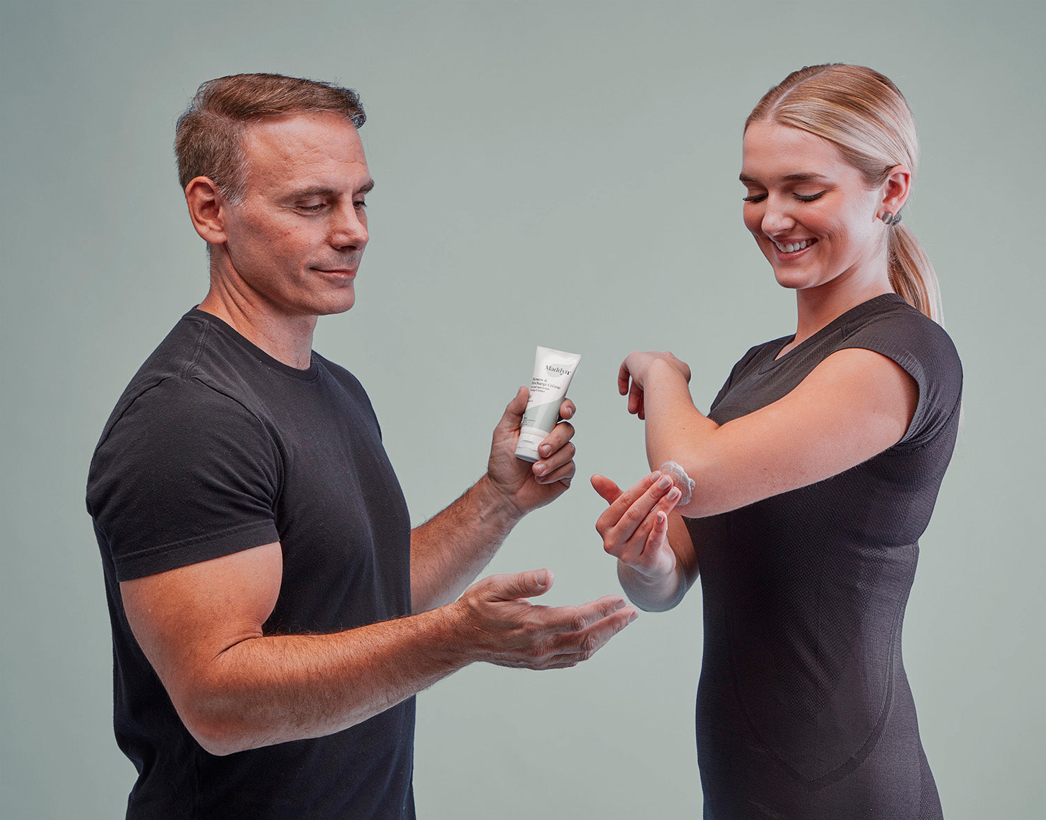Man giving woman Maddyn topical CBD cream for sore elbow