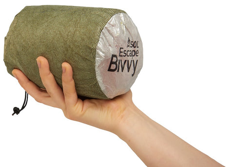SOL Escape Bivvy held in the palm of a hand to highlight compact size