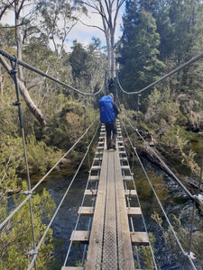 Hiker on suspension bridge wearing pack and pack cover