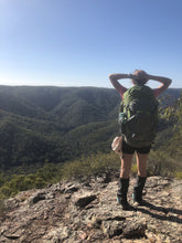 Load image into Gallery viewer, Young female hiker wearing Aarn pack on the top of a ridge overlooking a valley
