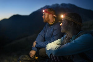 Two campers wearing Biolite head torches at night with the torch illuminated