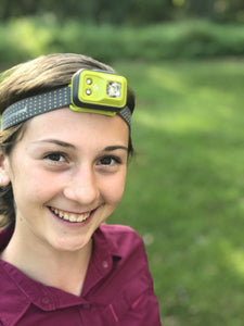 Young female smiling and wearing Black Diamond Cosmo head torch