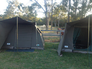 Two canvas safari tents pitched side-by-side at campsite with horse in background