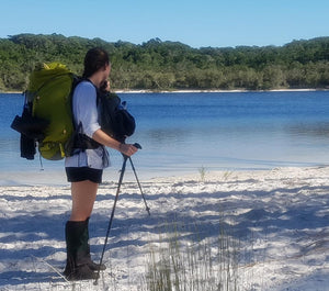 Female hiker wearing Aarn Hiking Pack with front pockets on the edge of a lake