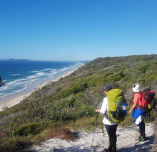 Load image into Gallery viewer, Two female hikers wearing packs at the top of a hill looking out towards the ocean