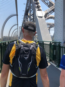 Man wearing Osprey Men's Duro 6 Race Vest Pack walking on bridge
