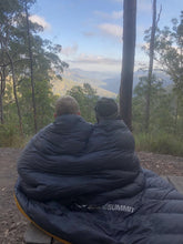 Load image into Gallery viewer, Two children wrapped in Sea to Summit quilt looking out over a valley
