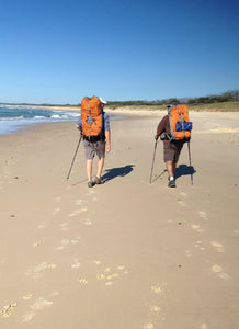 Two males wearing full hiking packs walking on the beach