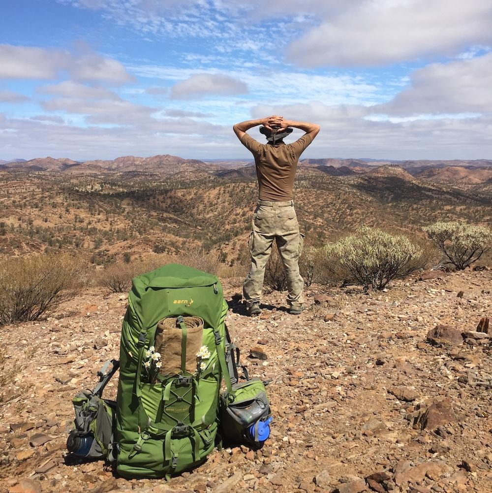 Man looking out over the South Australian desert with his Aarn hiking pack in the foreground