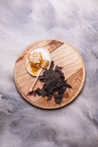 Kooee! Manuka Honey Beef Jerky placed on timber board next to raw honeycomb