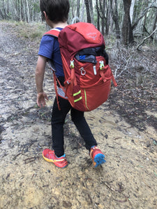 Young child wearing Osprey Jet 18 pack on walking trail surrounded by trees