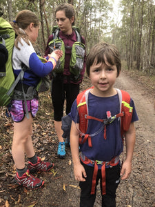 Child wearing Osprey Jet 18 pack front view with fellow hikers in background