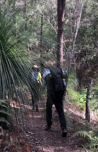 Male wearing Osprey Kestrel 58 Pack on hiking trail surrounded by trees