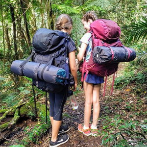 Two young girls wearing Osprey packs on hiking trail surrounded by palms and subtropical rainforest