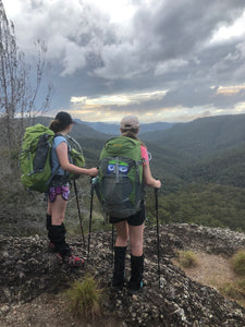 Two females using Pacer Poles at the top of a ridge overlooking a valley
