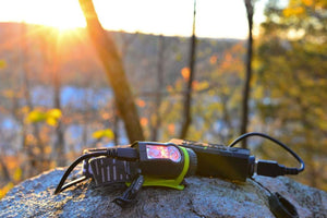 Princeton Tec AXIS Rechargeable Head Torch on rock attached to a power bank with USB charger cable