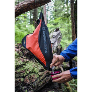 Sea To Summit Pack Tap 10L hanging from tree and being used to fill a mug
