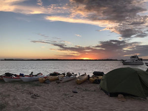 Luxe Habitat tent set up beside a row of kayaks on beach at sunset