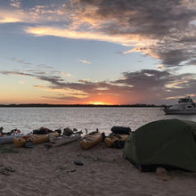 Load image into Gallery viewer, Luxe Habitat NX3 2-person hiking tent pitched on the beach next to a row of kayaks