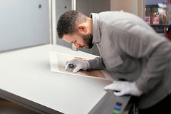 Man with magnifying glass at professional printers checking a photograph