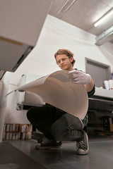 Man in professional photographic printers checking images