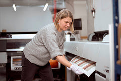 Woman removing a print sheet from machine at art printers