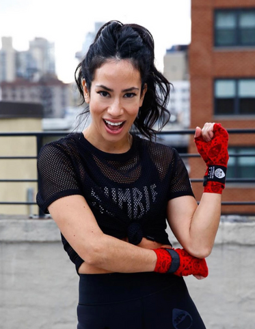 Mona Lavinia smiling in a black Rumble Boxing shirt and red boxing practice gloves.