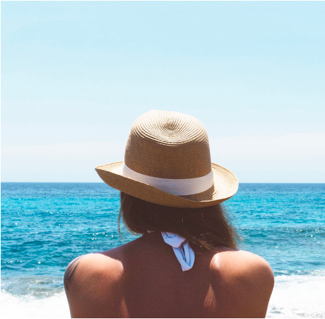 Woman on the beach in a straw hat looking out at the ocean.