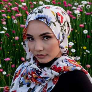 Woman in Hijab standing next to a filed of pink and white flowers wearing a floral hijab