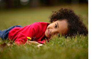 little girl in grass with dandelions