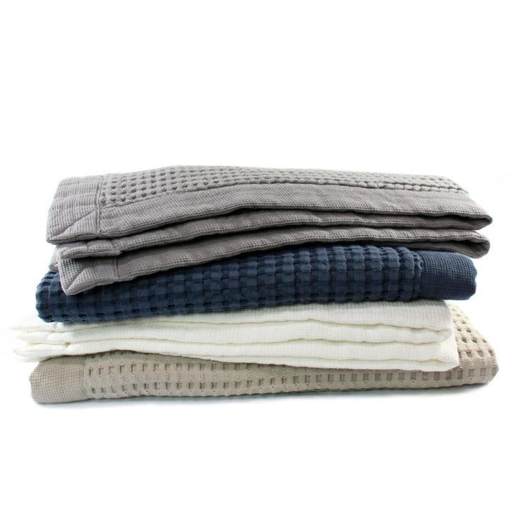 Waffle Bath Mats in a stack showing all four colors:  Slate, Midnight, White and Pewter