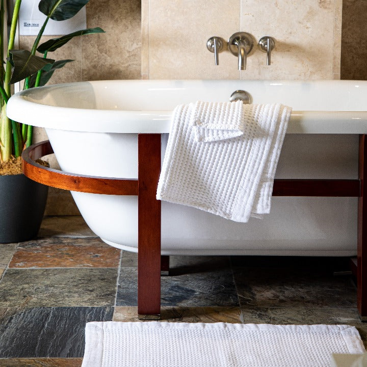 Beautiful image of modern bathroom showing waffle weave bath mat and waffle weave bath towels.