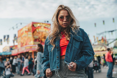 Woman wearing a denim jacket at an amusement park