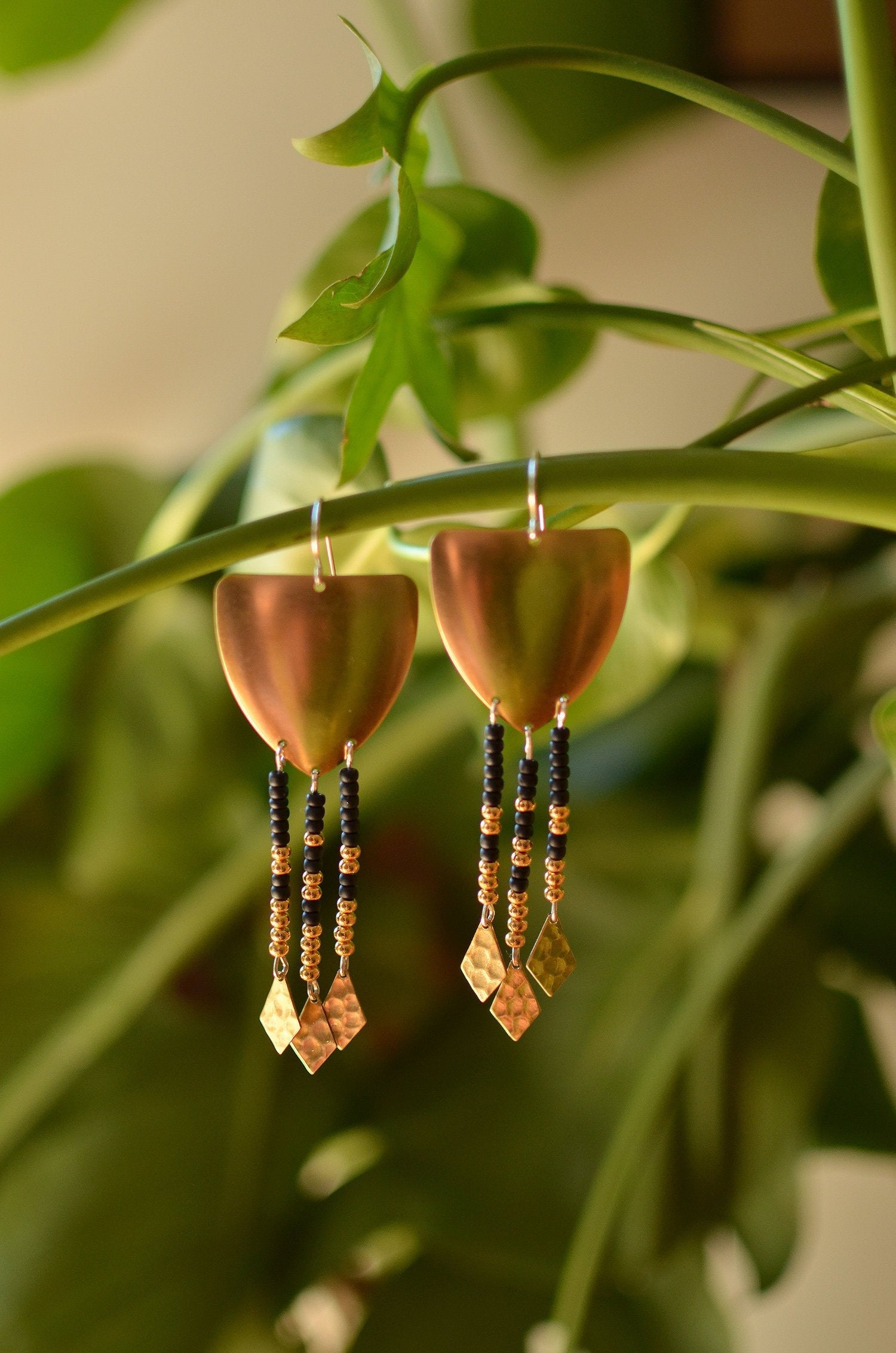 warrior woman. one pair raw brass shield earrings with seed bead dangles & gleaming hammered points.