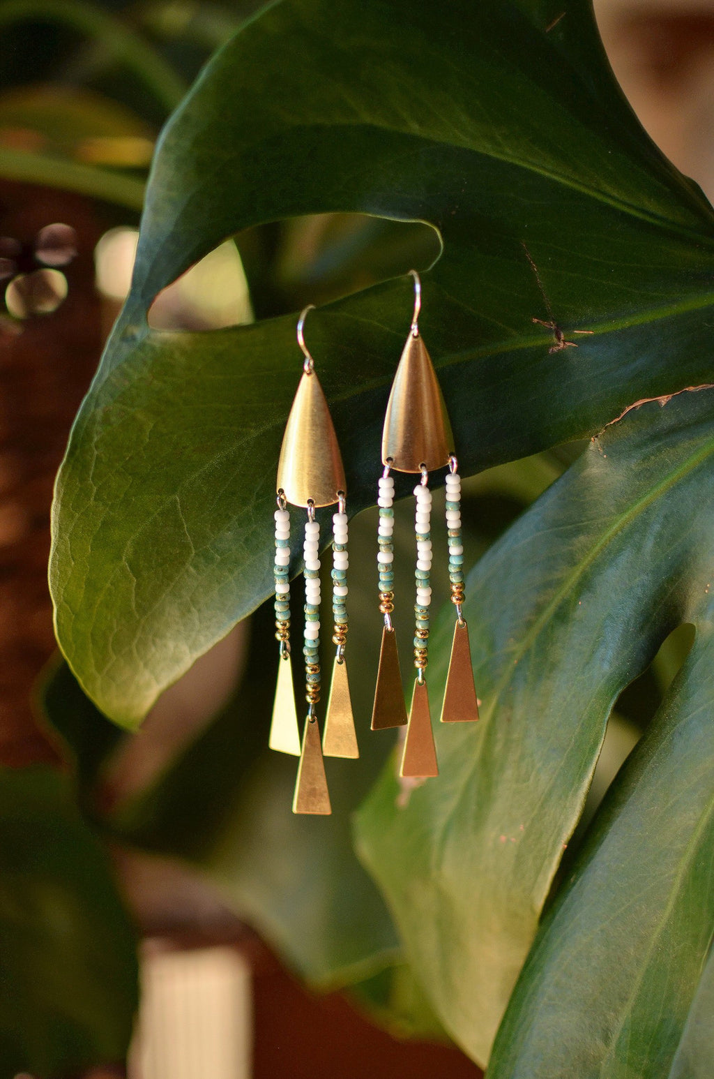 warrior woman. one pair raw brass shield earrings with seed bead dangles & gleaming triangles.