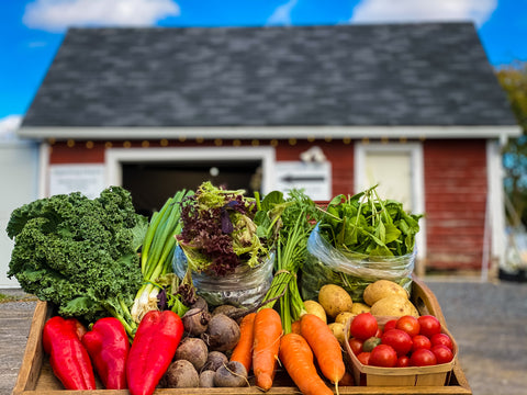 fresh organic vegetables laid out on a wooden trap in the foreground and a red with white trim farm store in the background