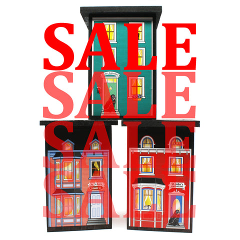 three wooden houses with SALE text in front of them