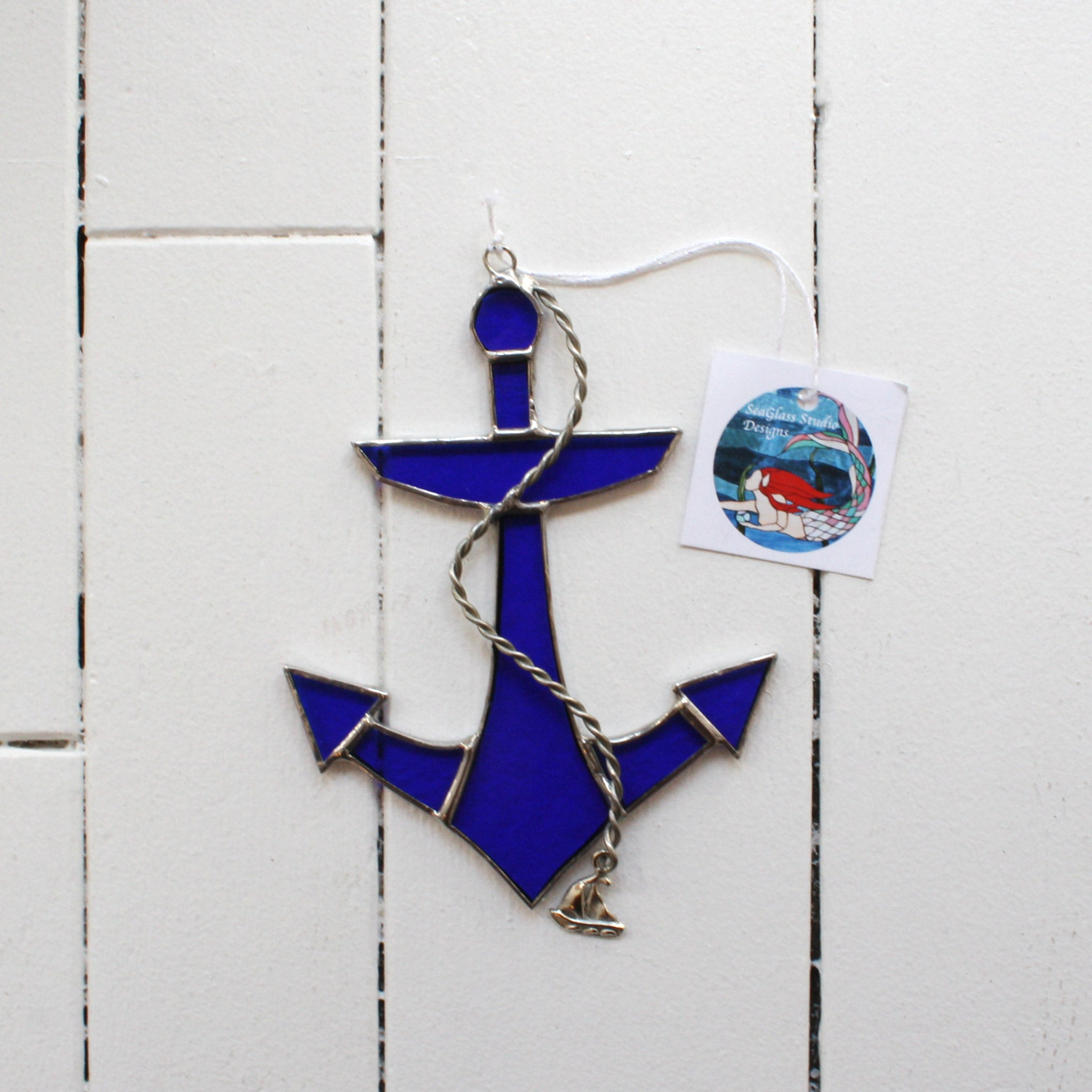 textured clear blue stained glass anchor with attached nautical themed decoration