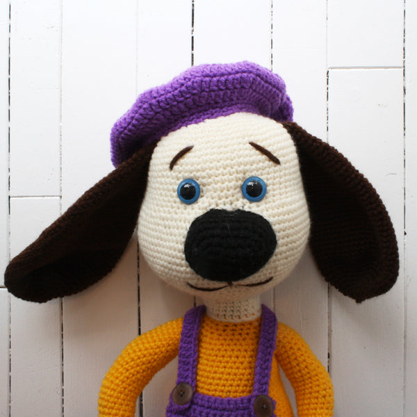 crocheted dog with floppy ears dressed in artist outfit