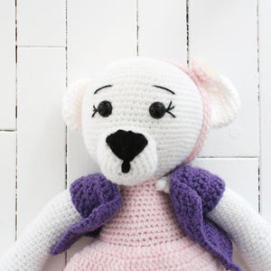 A crocheted white bear with a pink and purple outfit