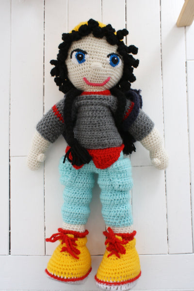 plush toy with black hair, yellow cap, grey sweater, and blue pants